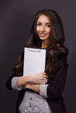 Portrait of  business woman with paper folder. Studio shot of an attractive young businesswoman Royalty Free Stock Photography