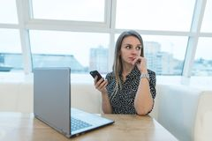 Portrait of a business woman with a phone in her hands sitting on a white laptop in a restaurant with a stylish design. The freelancer works in a cafe. Look Stock Image