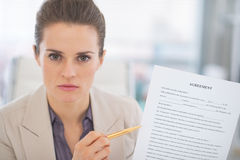 Portrait of business woman pointing on document Stock Photos