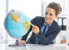 Portrait of business woman pointing on earth globe. Portrait of happy business woman pointing on earth globe stock photography