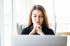 Portrait of business woman resting chin on hand in front of her laptop at office Stock Photos