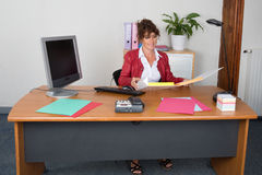 Portrait of a business woman sitting at desk Stock Photos