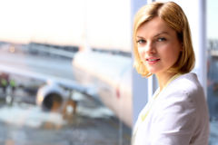 Portrait of business woman standing  near window. Airplane background behind. Royalty Free Stock Image