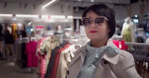 Portrait of a business woman in sunglasses in a clothing boutique, looking at the camera and smiling, slow motion