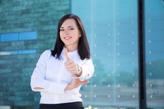 Portrait of business woman thumbs up in street Stock Image