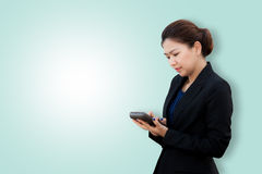 Portrait of business woman using calculator on color background Stock Photo