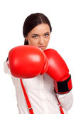 Portrait of business woman wearing boxing gloves Stock Photo