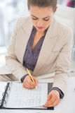 Portrait of business woman writing in document. In office Royalty Free Stock Photo