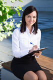 Portrait of business woman writing something on clipboard in cit Royalty Free Stock Image