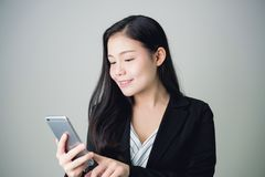 Portrait of Business women in suit are touching a smartphone in hand to use the Internet to find information online. Portrait of Business woman in suit are Royalty Free Stock Photo