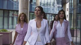 Portrait of business women walking in the city. Close up portrait of five attractive business women walking near business centre. Summer day. Color grading stock video footage