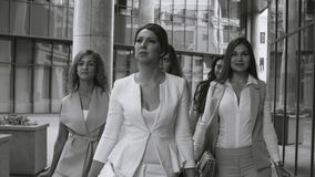 Portrait of business women walking in the city. Close up portrait of five attractive business women walking near business centre. Summer day. Black and white stock footage