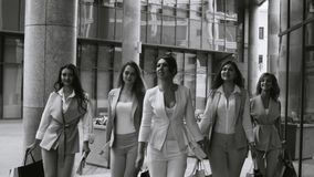 Portrait of business women walking in the city. Close up portrait of five attractive business women walking near business centre. Summer day. Black and white stock video