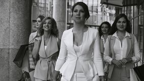 Portrait of business women walking in the city. Close up portrait of five attractive business women walking near business centre. Summer day. Black and white stock video footage