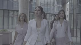 Portrait of business women walking in the city. Close up portrait of five attractive business women walking near business centre. Summer day. No grading version stock video footage