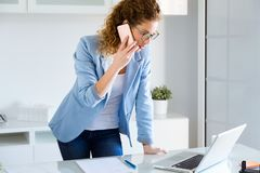 Business young woman talking on the mobile phone while using her laptop in the office. Stock Photography
