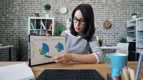 Portrait of businesslady talking showing chart during video conference in office. Portrait of businesslady in glasses talking showing chart during video stock footage
