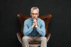Portrait of businesslike gentleman 50s with grey hair and beard. In glasses sitting on wooden armchair with severe look isolated over black background Royalty Free Stock Images