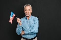 Portrait of businesslike gentleman 50s with grey hair and beard. In shirt seriously holding small american flag isolated over black background Royalty Free Stock Image