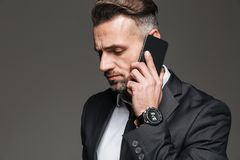 Portrait of businesslike guy in black suit talking on smartphone. With watch on wrist isolated over dark gray background Stock Image