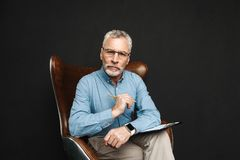 Portrait of businesslike middle aged man 50s with grey hair and. Beard working with documents while sitting on wooden armchair in office isolated over black Stock Photo