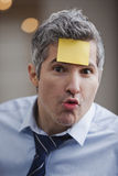 Portrait of a businessman with adhesive note on forehead Royalty Free Stock Images