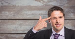 Portrait of businessman aiming forehead with finger against wooden wall. Digital composite of Portrait of businessman aiming forehead with finger against wooden Royalty Free Stock Photography