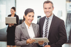 Portrait of businessman and businesswoman holding digital tablet Stock Photos