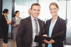Portrait of businessman and businesswoman holding file Stock Photo