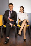 Portrait of businessman and businesswoman sitting in waiting room Stock Photos