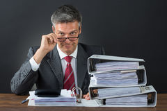 Portrait Of Businessman Checking Invoice At Desk. Portrait of confident businessman checking invoice at desk against gray background Royalty Free Stock Images