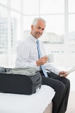 Portrait of a businessman with coffee cup reading newspaper by luggage. Side view portrait of a mature businessman with coffee cup reading newspaper by luggage Royalty Free Stock Images