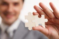 Portrait Businessman connecting puzzle pieces. Concept. in a studio. Stock Photos