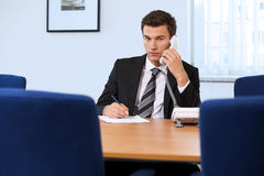 Portrait of businessman conversing on landline phone Stock Images