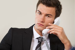 Portrait of businessman conversing on landline phone Stock Photography