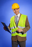 Portrait of businessman in coveralls holding clipboard and showing thumbs up sign Stock Photography