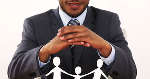 Portrait of businessman with cutout paper chain family with the protection of hands. On table in office 4k stock video