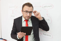 Portrait of a businessman with a digital tablet. Flowchart in the background. Stock Image