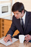 Portrait of a businessman drinking coffee while reading a newspaper Stock Images