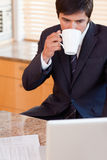 Portrait of a businessman drinking coffee while using a laptop Stock Photos