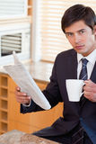 Portrait of a businessman drinking tea while reading a newspaper Stock Photos