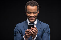 Portrait of businessman in formalwear typing on smartphone. Isolated on black Royalty Free Stock Photos
