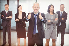 Portrait of businessman giving thumbs up and business people standing with arms crossed Royalty Free Stock Image