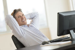Portrait Of Businessman With Hands Behind Head Relaxing At Desk Stock Image