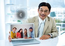 Portrait of businessman having video call with colleagues on laptop in office. Portrait of smiling businessman having video call with colleagues on laptop in Royalty Free Stock Photo