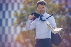Portrait of businessman holding blazer and newspaper Stock Photo