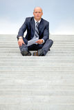 Portrait of businessman holding document on steps Stock Images
