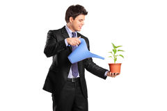 Portrait of a businessman holding a flower and can Stock Image