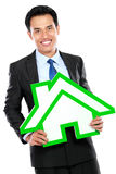 Portrait of businessman holding house sign. Property conceptual Royalty Free Stock Photos