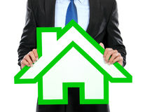 Portrait of businessman holding house sign. On white background Royalty Free Stock Photography